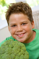 smiling boy holding head of broccoli